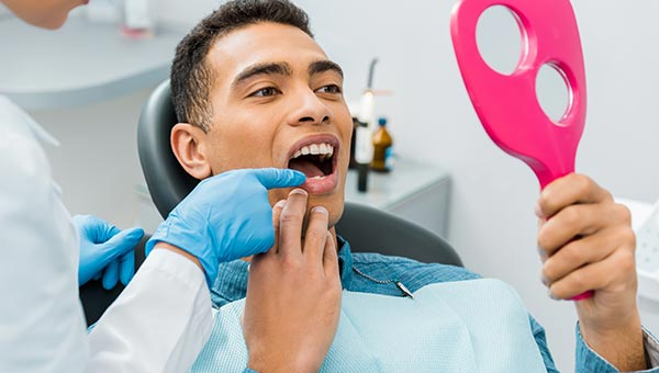 man in dentist chair with mirror