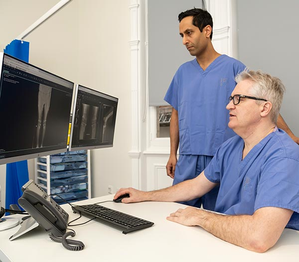 Two surgeons looking at xray's on a computer