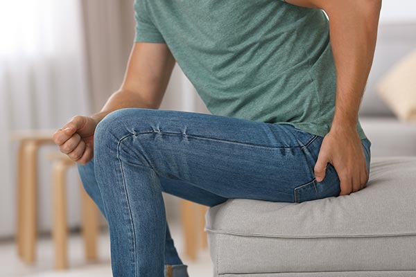 man sitting with hand on backside
