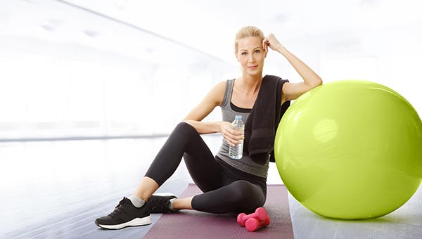 Middle aged woman sitting on the floor with fitness ball