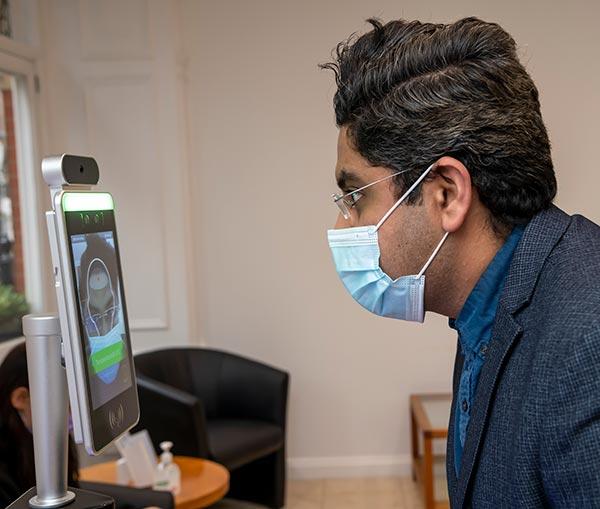 Examining patient through heat sensor for temperature
