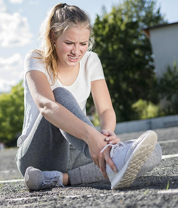 Young woman with ankle pain