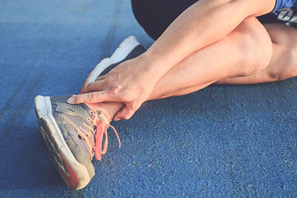 Male runner on the floor holding his ankle