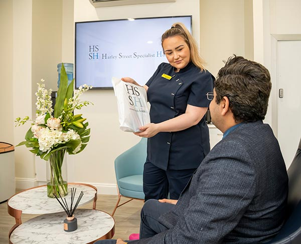 Receptionist presents a bag to a patient in a waiting room