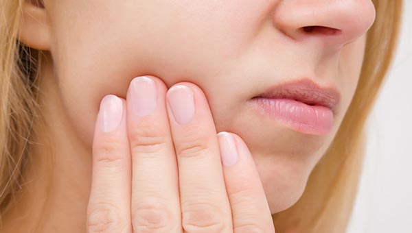 Close up of woman holding jaw in pain