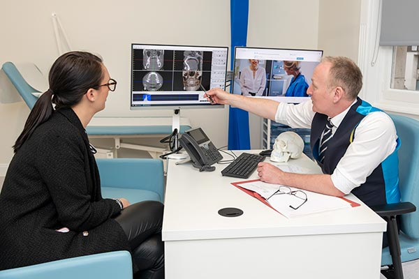 Mr Luke Cascarini showing a patient their xray at an HSSH consulting room