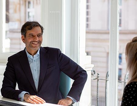 Consultant Mr Ali Noorani sat at desk talking to female patient