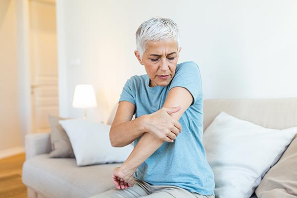 Senior woman holding her elbow
