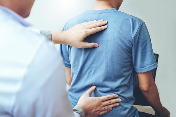 Consultant with hands on the back of a patient